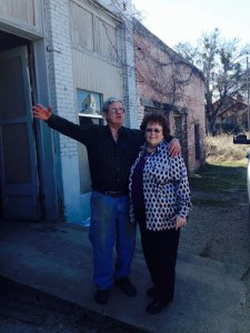 "Mom and Pop at his shop downtown Iredell.  He's saying hi to somebody who'd stopped in the road to shout ""Hey""."